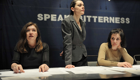 three women sit and stand behind a desk. On the wall behind them it says SPEAK BITTERNESS
